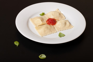 Russian ravioli - pelmeni with tomato sauce and basil on a white