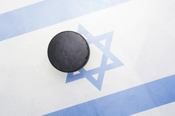 old hockey puck is on the ice with israel flag