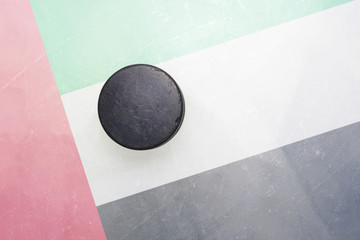 old hockey puck is on the ice with united arab emirates flag