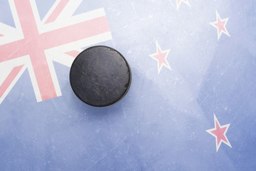 old hockey puck is on the ice with new zealand flag