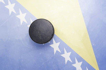 old hockey puck is on the ice with bosnia and herzegovina flag