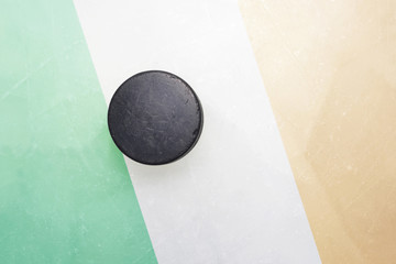 old hockey puck is on the ice with ireland flag