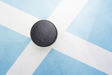 old hockey puck is on the ice with scotland flag