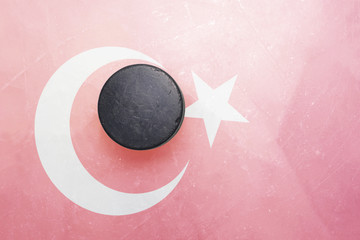 old hockey puck is on the ice with turkey flag