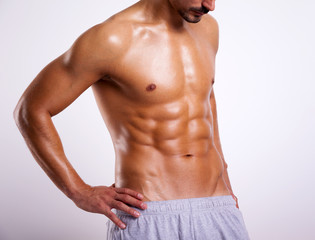 Fitness man showing six pack abs on grey background