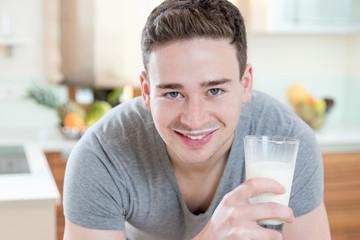 Junger lächelnder Mann mit Milchbart