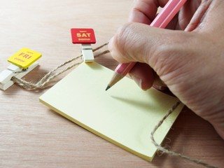 Taking note on yellow paper with attached red wooden paper clip, Saturday tag