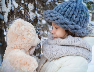 Little girl looking at a soft teddy bear in a winter park