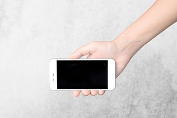 Hand with mobile smart phone Isolated on cement wall background