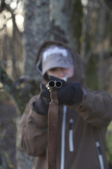 Image of a young person with shotgun