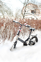Winter in the city. Bicycle covered with snow.