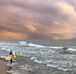 Female surfer on the beach at the sunset with stormy sea and surfboard