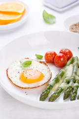 Fried egg with asparagus and tomatoes on a white plate with blue napkin. ..