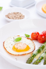 Fried egg with asparagus and tomatoes on a white plate with blue napkin. closeup..