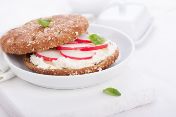 Sandwich with wholewheat bread, cottage cheese, radish and basil on a white plate, closeup, selective focus..