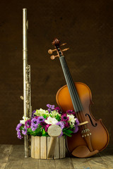 Silver flute and violin on old steel background