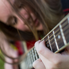 Fingers on the strings of the guitar, the face of a young girl in the blur.
