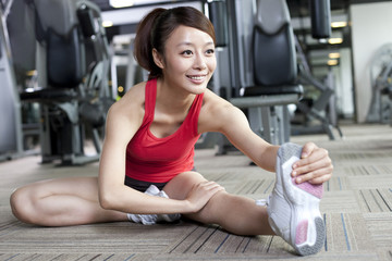 Young woman stretching in gym