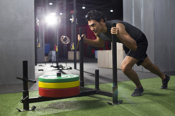 Young man pushing weight sled at gym
