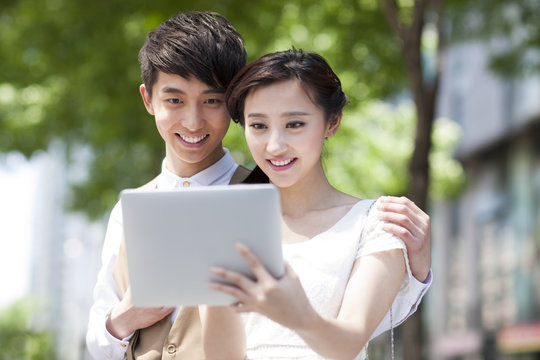 Happy young couple with digital tablet
