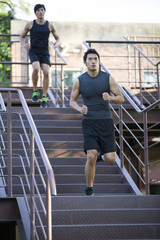 Young joggers running down steps outdoors