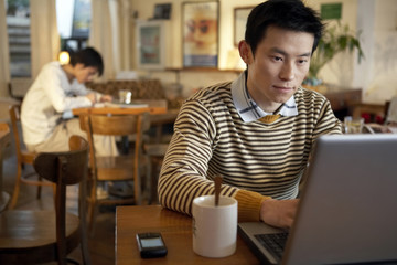 Young Man Sitting In Cafe On Laptop Computer
