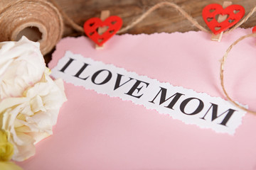 Congratulation card and flowers for mother's day on wooden background
