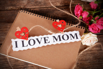 Notebook for mother's day and flowers on wooden background