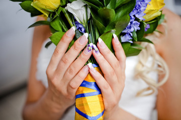 Wedding bouquet of roses manicure and yellow and blue