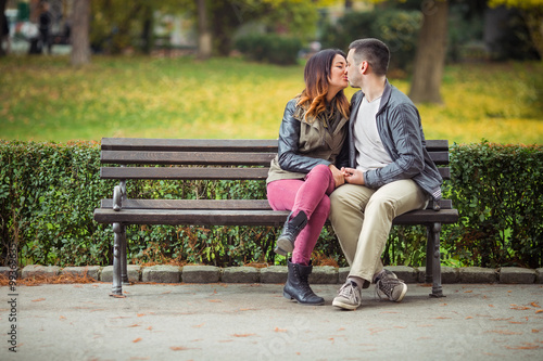 Beautiful Couple Kissing While Sitting On A Park Bench Stock Photo