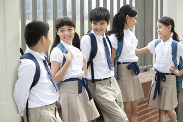 Cute schoolchildren in uniform leaning against a fence