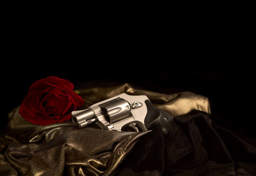 Snubnose 38 revolver laying across gold satin with a red rose and black velvet