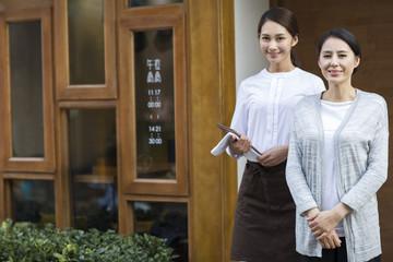 Restaurant owner and waitress standing in doorway