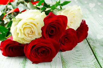 Red and white roses on wooden background