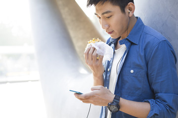 Young man listening to earphones and eating food