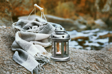 Decorative lamp, basket and plaid on rock in the forest, close up