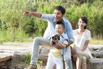Happy Chinese family with camera photographing in a park