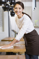 Portrait of waitress cleaning table at restaurant