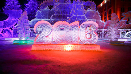 Happy new year 2016 written with ice letters, sculptures in the park beautiful illumination at night.