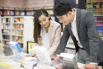Young couple choosing books in bookstore