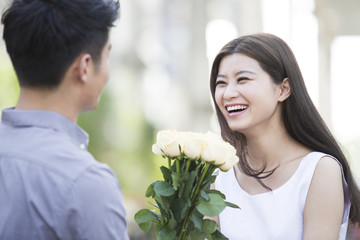 Young man giving flowers to girlfriend