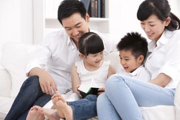 Happy family reading book in sofa