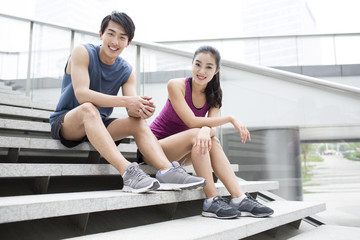 Young couple resting on the stairs after exercise