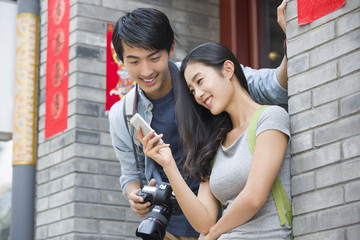 Happy young couple holding smart phone and camera
