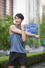 Young man stretching outdoors