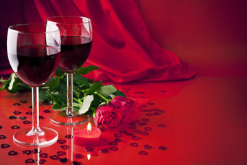 Glasses with wine, a candle and roses