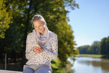 frau sitzt draußen am wasser und tippt eine sms