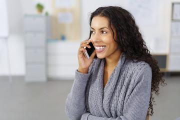 lächelnde frau im büro telefoniert mit ihrem smartphone