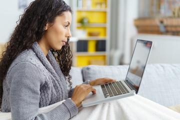 frau sitzt gemütlich auf dem sofa und surft im internet
