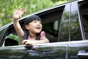 Cheerful girl waving out of car window